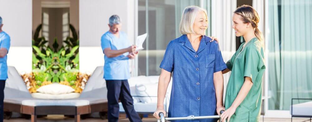 caregiver holding the shoulder of patient in a walker