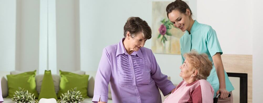 two elderly with a caregiver